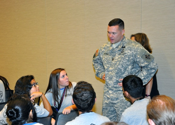 Capt. Adam Z. McGinnis, the U.S. Army Corps of Engineers Los Angeles District's deputy area engineer for the Arizona-Nevada Area Office, speaks with a group of students from Phoenix area schools during a Science Technology Education and Math event held Sept. 25 at the Phoenix Convention Center by Ten80 Education. The event was one of ten expositions Ten80 held across the country in 2014 where students actively engage in workshops, demonstrations and a one-day points race for pride and prizes and both students and teachers could evaluate the National STEM League curriculum, collaborative network and optional competition league.