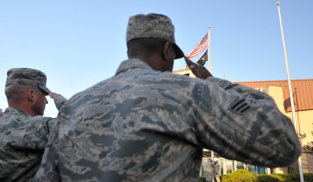 Airmen salute the flags during the POW/MIA remembrance ceremony Sept. 19, 2014 on Osan Air Base, Republic of Korea. This annual event honors the prisoners of war and those who went missing in action. (U.S. Air Force photo by Senior Airman David Owsianka)