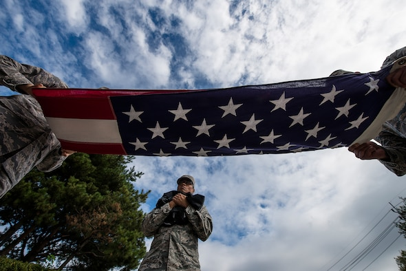 Team Osan Airmen fold the United States flag after a retreat ceremony Sept. 24, 2014, at Osan Air Base, Republic of Korea. The retreat ceremony was part of the base's Prisoners of War/Missing in Action remembrance week. (U.S. Air Force photo by Staff Sgt. Jake Barreiro/Released)