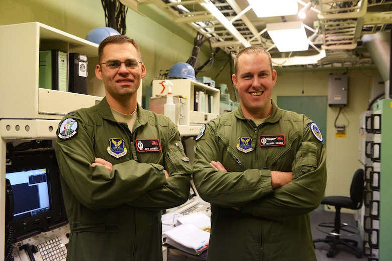 1st Lt. Jeff Cumber, 12th Missile Squadron deputy missile combat crew commander (left), and Capt. Dan Hejde, 12th MS combat missile crew commander, pose for a photograph after a training session at Malmstrom Air Force Base Sept. 24. The team is one of nine from the base that will be competing in the 2014 Air Force Global Strike Challenge. (U.S. Air Force photo/Airman 1st Class Collin Schmidt)