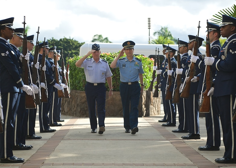 Gen. Hawk Carlisle, Pacific Air Forces commander (left), and Lt. Gen. Huang Guoxian (right), commander Nanjing Military Regional Air Force Command, render salutes while passing through an honor guard cordon, Sept. 23, 2014, Joint Base Pearl Harbor-Hickam, Hawaii.  Carlisle hosted Huang and a delegation of People's Liberation Army Air Force officers as part of a reciprocal visit key to building a strong military to military relationship between the U.S. and China. (U.S. Air Force photo by Tech. Sgt. James Stewart/Released)