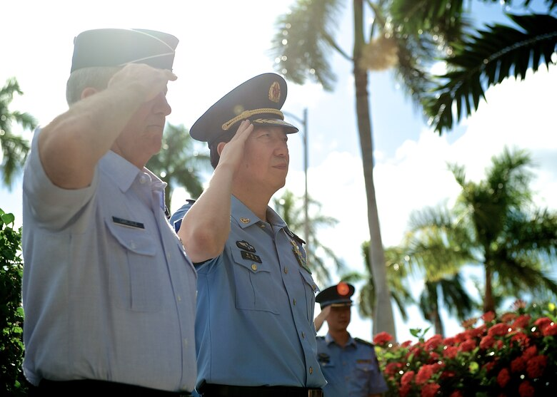 Gen. Hawk Carlisle, Pacific Air Forces commander (left), and Lt. Gen. Huang Guoxian (right), commander Nanjing Military Regional Air Force Command, render salutes before passing through an honor guard cordon, Sept. 23, 2014, Joint Base Pearl Harbor-Hickam, Hawaii.  Carlisle hosted Huang and a delegation of People's Liberation Army Air Force officers as part of a reciprocal visit key to building a strong military to military relationship between the U.S. and China. (U.S. Air Force photo by Tech. Sgt. James Stewart/Released)