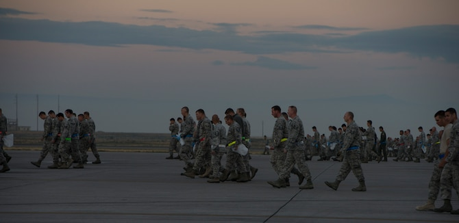 Service members from Mountain Home Air Force Base, Idaho, gather to pick up debris left behind from the open house in a wing-wide FOD walk on the flightline Sept. 22, 2014. Airfield management coordinated the event to get everyone involved in cleaning up the flightline. (U.S. Air Force photo by Airman 1st Class Jessica Smith/ RELEASED)