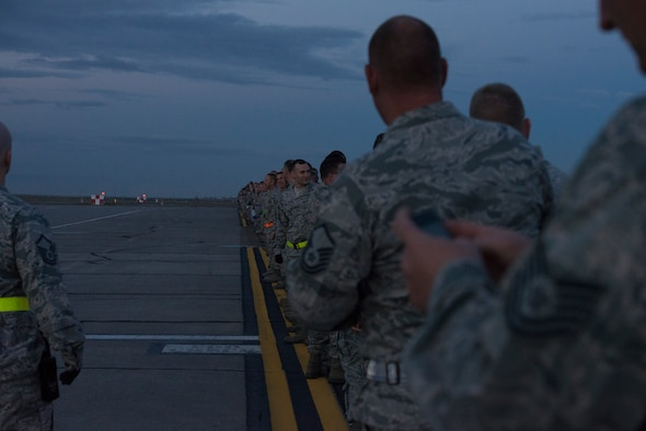 Service members of Mountain Home Air Force Base, Idaho, gather early in the morning to assist in a wing-wide FOD walk on the flightline, Sept. 22, 2014. Airfield management helped coordinate the event to get the flightline cleared for operation. (U.S. Air Force photo by Airman 1st Class Jessica Smith/RELEASED)