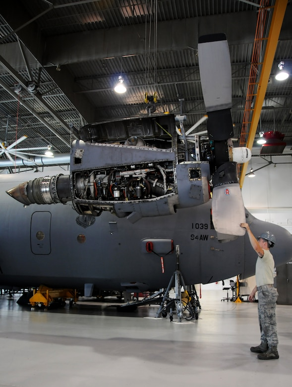 Senior Airman Ian McKibbin, 94th Maintenance Squadron aerospace propulsion technician, guides the engine of a C-130 Hercules as it is hoisted to be placed into the wing of the aircraft at Dobbins Air Reserve Base, Ga., Sept. 25, 2014. A team of 44 Airmen and one C-130 are preparing to venture off to be a part of RED FLAG-Alaska 15-1. (U.S. Air Force photo by Senior Airman Daniel Phelps/Released)