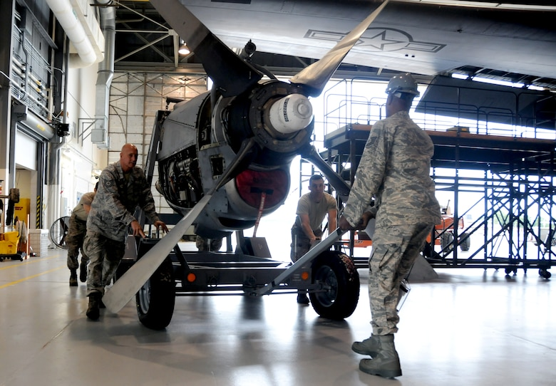 Airmen of the 94th Maintenance Squadron move the engine of a C-130 Hercules at Dobbins Air Reserve Base, Ga., Sept. 25, 2014. On Sept. 29, the 94th Airlift Wing is sending one C-130 and a team of 44 Airmen to partake in RED FLAG-Alaska 15-1. (U.S. Air Force photo by Senior Airman Daniel Phelps/Released)