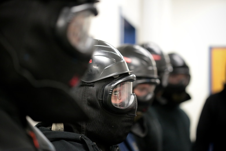 A picture of New Jersey Air National Guard, U.S. Coast Guard, and local law enforcement officers listening to a debrief.