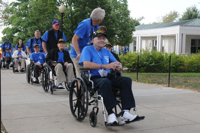 World War II veterans are escorted into the the World War II Memorial in Washington, D.C., Sept. 19, 2014. The group consisted of 66 veterans that made the journey from Utah to see their memorial, many for the first time.(U.S. Air Force photo by Senior Master Sgt. Gary J. Rihn/Released)