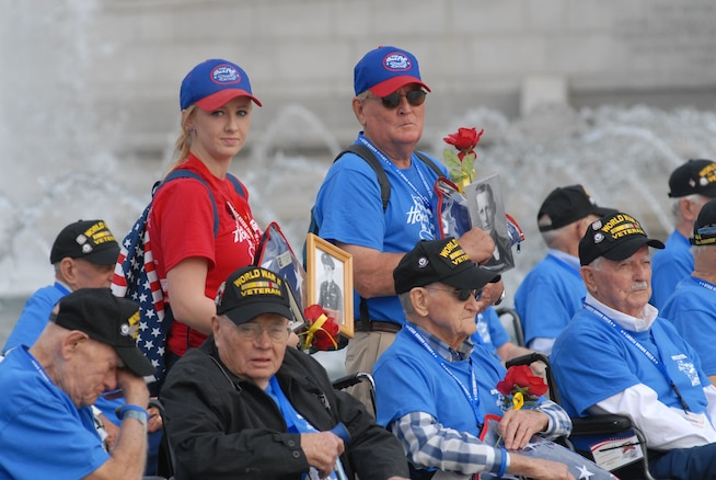 World War II veterans gather for a group photo at the World War II Memorial in Washington, D.C., Sept. 19, 2014. Family members standing amongst veterans also held portraits of recently passed veterans. The veterans were part of a group of 66 that were there to see their memorial, many for the first time.(U.S. Air Force photo by Senior Master Sgt. Gary J. Rihn/Released)