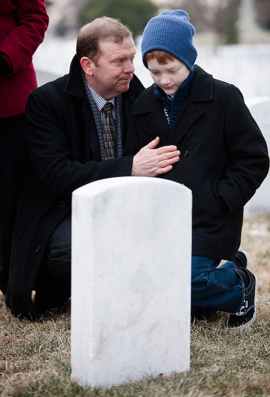 Scobee and his son, Andrew, kneel near the grave of Dick Scobee earlier this year during the NASADay of Remembrance. Dick Scobee was the commander of the Space Shuttle Challenger, which exploded shortly after launch in 1986. His grave is near the memorials to the Space Shuttles Challenger and Columbia in Arlington National Cemetery's Section 46.