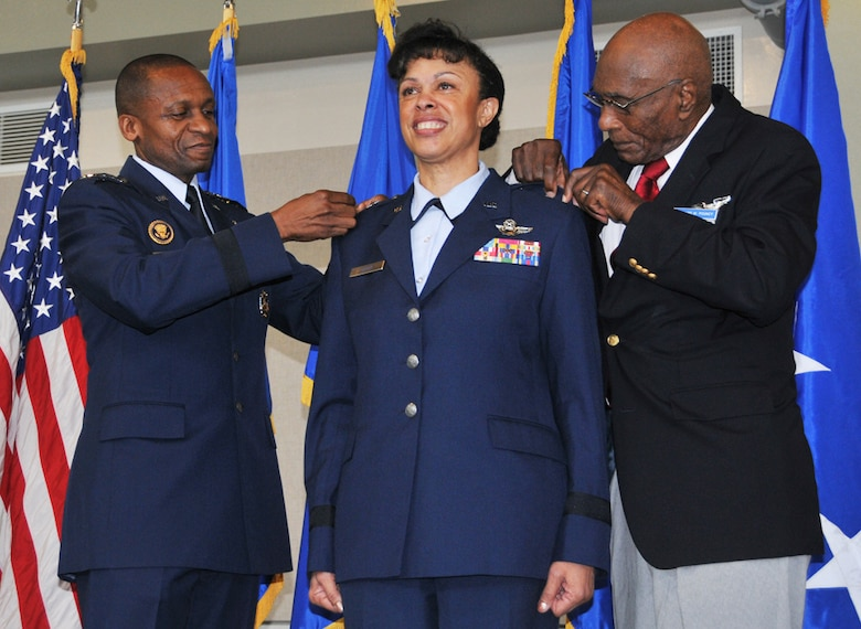 Gen. Darren W. McDew, Air Mobility Command commander, and Hillard W. Pouncy, an original Tuskegee Airman, pin stars on Harris during her recent promotion ceremony. (Staff Sgt. Jaclyn McDonald)