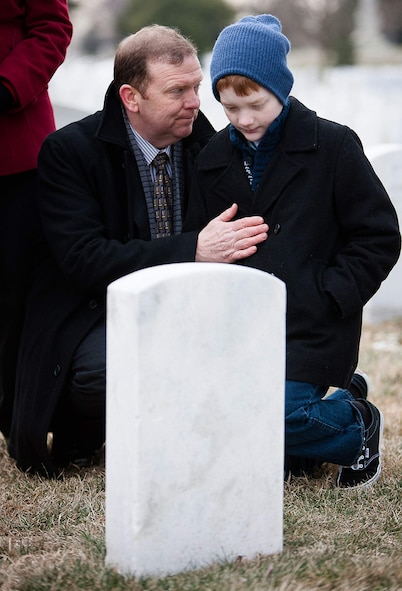 Scobee and his son, Andrew, kneel near the grave of Dick Scobee earlier this year during the NASA Day of Remembrance. Dick Scobee was the commander of the Space Shuttle Challenger, which exploded shortly after launch in 1986. His grave is near the memorials to the Space Shuttles Challenger and Columbia in Arlington National Cemetery's Section 46.