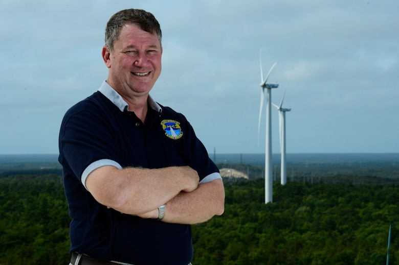 Steve Mellin, 6th Space Warning Squadron support officer, stands before two wind turbine power generators on Cape Cod Air Force Station, Mass., Sept. 11, 2014. The two wind turbines provide Cape Cod AFS with nearly 50 percent of their power needs and helps save the Air Force more than $600,000 annually. (U.S. Air Force photo by Airman 1st Class Krystal Ardrey)