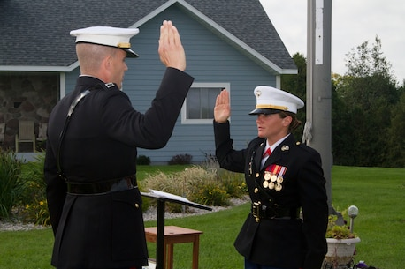 Capt. Chad Luebke, Officer Selection Officer of Recruiting Station Milwaukee, administers the Officer Oath of Office to 2nd Lt. Louise Nowak during her commissioning ceremony in Pound, Wis., on Sept. 20, 2014.  Nowak, a recent graduate of Carroll University, was awarded the Commandant's Trophy earlier this year in recognition of her exceptional academic performance, physical fitness and leadership at Officer Candidate School in Quantico, Va.