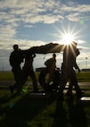 """A team carries an """"injured"""" teammate, jerry cans of water and tires to the next station Sept. 26, 2014, during the Monster Mash on RAF Mildenhall, England. The Monster Mash consisted of various events such as carrying an inflatable boat, marching with a 40-pound rucksack and a blind weapons assembly. A Monster Mash is a long-standing special tactics tradition which combines events designed to test strength, stamina and problem solving skills. (U.S. Air Force photo/Tech. Sgt. Stacia Zachary/Released)"""