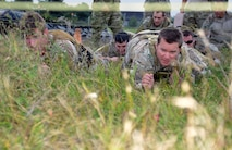 U.S. Air Force Master Sgt. Tim Garlock, right, 321st Special Tactics Squadron combat controller, and U.S. Air Force Staff Sgt. Alan Abraham, 321st STS combat controller, navigate a high- and low-crawl station during the Monster Mash Sept. 26, 2014, on RAF Mildenhall, England. The Monster Mash consisted of various events such as carrying an inflatable boat, marching with a 40-pound rucksack and a blind weapons assembly. A Monster Mash is a long-standing special tactics tradition which combines events designed to test strength, stamina and problem solving skills. (U.S. Air Force photo/Tech. Sgt. Stacia Zachary/Released)