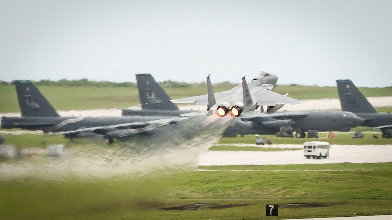 An F-15C Eagle takes off in front of B-52 Stratofortesses during Valiant Shield 2014, at Andersen Air Force Base, Guam, Sept. 16, 2014. Valiant Shield is a U.S.-only exercise, integrating Navy, Air Force, Army and Marine Corps assets, offering real-world joint operational experience to develop capabilities that provide a full range of options to defend U.S. interests and those of its allies and partners.  (U.S. Air Force Photo by Staff Sgt. William Banton)