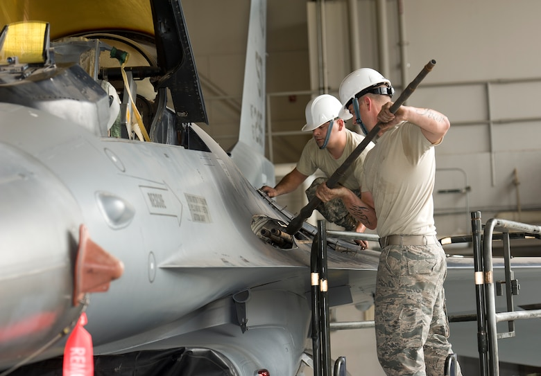 Tech. Sgt. Hunter Pettit and Tech. Sgt. Shiloh Blanco, remove and install an M61A1 20mm gun on an F-16 to acquire the firing solenoid for future training of armament students on Sept. 18, 2014 at Sheppard Air Force Base, Texas. Pettit and Blanco are instructors with the 363rd Training Squadron. The parts removed from the aircraft will be used for M61A1 gun training for over 120 students for fiscal year 2015 without having to spend money on parts.  (U.S. Air Force Photo Danny Webb)