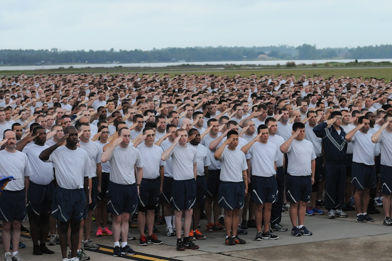 Airmen from Keesler Air Force Base, Miss., render a salute as the National Anthem is sung prior to the start of a 5K run on the flight line Sept. 19, 2014. The run was the kickoff event for a day full of activities supporting Wingman Day. (U.S. Air Force photo by Kemberly Groue)