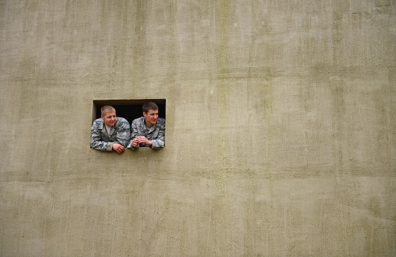 Airmen from the 48th Mission Support Group watch a training exercise from a building constructed as a mock village during a force-on-force exercise at Stanford Training Area, England, Sept. 19, 2014. More than 130 48th MSG Airmen participated in the training exercises and practiced scenarios they could possibly encounter in a deployed environment. (U.S. Air Force photo by Airman 1st Class Erin O'Shea)