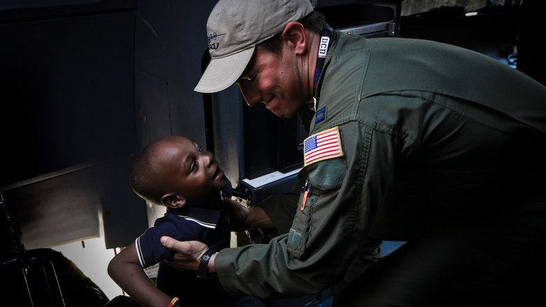 Capt. Lindsey Kinsinger helps a child into the flight deck of a C-130J Super Hercules at the Africa Aerospace & Defence Expo at Waterkloof Air Force Base, South Africa, Sept. 20, 2014.  The C-130, from the 37th Airlift Squadron, was part of a total-force team of Guard, Reserve and active-duty Soldiers and Airmen at the expo. Air show attendees were given an opportunity to view the inside of an Air Force C-130J and C-17 Globemaster III. (U.S. Air Force photo/Staff Sgt. Travis Edwards)