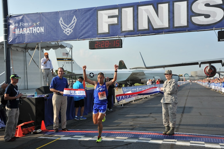 """Steve Chu crosses the finish line as the 2014 U.S. Air Force Marathon Men's full marathon champion at Wright-Patterson Air Force Base, Ohio, Sept 20. """"I wanted to win this for my wife,"""" said Chu, whose wife is an active duty Air Force major. (U.S. Air Force photo by Mike Libecap)"""
