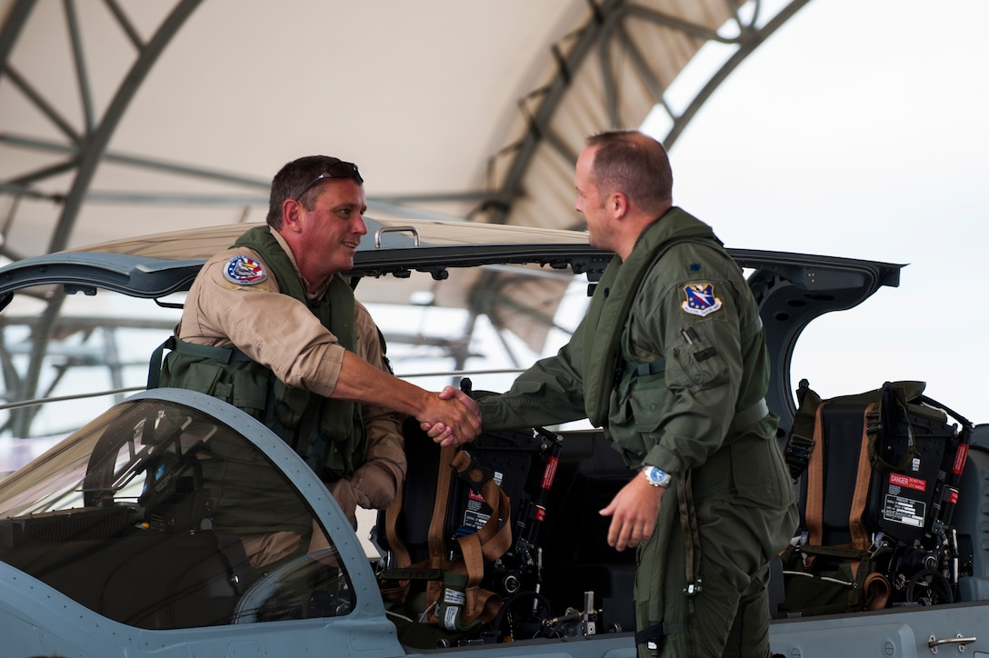 Chris Carlson, left, Sierra Nevada Corporation senior pilot, shakes hands with Lt. Col. Jeffrey Hogan, Afghan A-29 Light Air Support training unit commander, after landing an A-29 Super Tucano for its first arrival Sept. 26, 2014, at Moody Air Force Base, Ga. Moody was selected for the A-29 LAS training mission to train a total of 30 Afghan pilots and 90 Afghan maintainers over the next four years. (U.S. Air Force photo/Airman 1st Class Dillian Bamman)