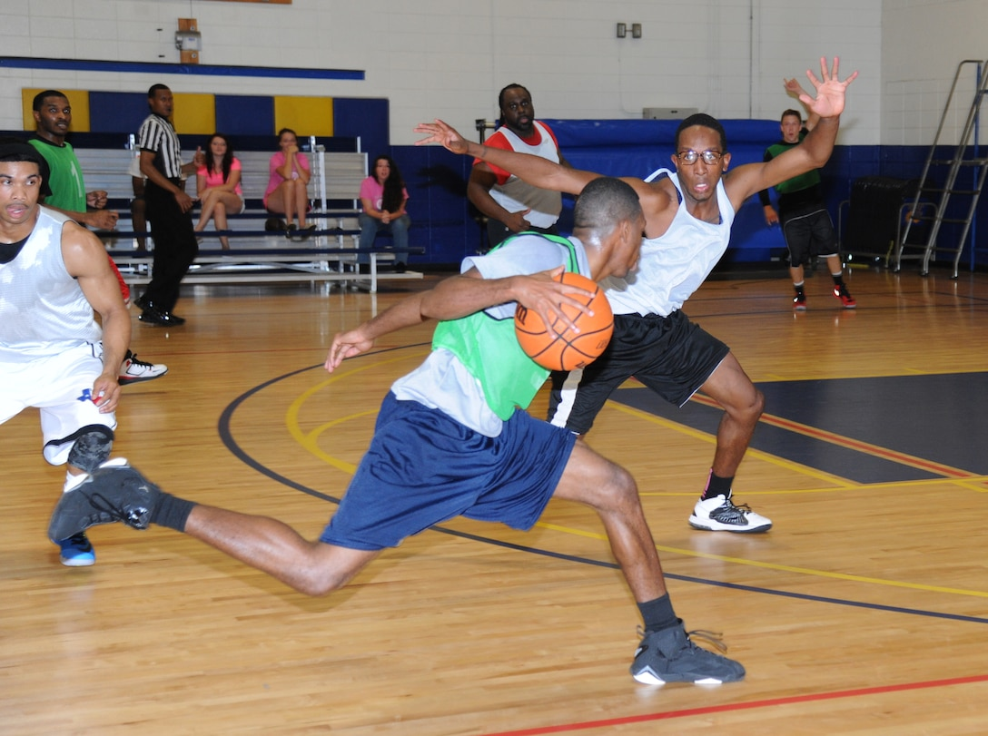 Gregory Jernigan, 81st Diagnostic and Therapeutics Squadron, drives the ball towards the basket as Marquez Barr, 81st Medical Group protects the inside during the intramural basketball championship game Sept. 25, 2014, at the Blake Fitness Center, Keesler Air Force Base, Miss.  The 81st MDG defeated the 81st MDTS, 41-37.  (U.S. Air Force photo by Kemberly Groue)