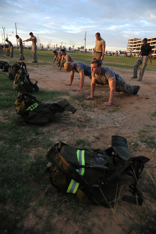 Members of the 334th Training Squadron combat controllers and the 335th Training Squadron special operations weather team participate in a memorial physical training session Sept. 26, 2014, Biloxi, Miss., with burpees and a ruck march along the Ocean Springs Beach and over the Biloxi/Ocean Springs Bridge. The PT event was in memory of combat controller Senior Airman Mark Forester who was killed in action Sept. 29, 2010, and Senior Airman Daniel Sanchez who was killed in action Sept. 16, 2010.  (U.S. Air Force photo by Kemberly Groue)