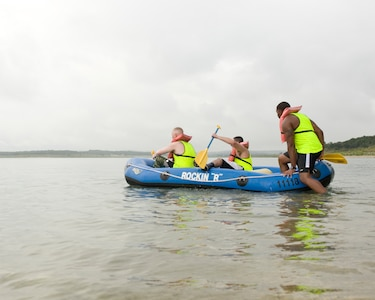 At the Rambler 120 Adventure Race at Joint Base San Antonio Recreation Park, Sept. 20, 2014, teammates come together to finish the final of three strenuous legs of the race. The overcast weather at Canyon Lake provided some relief for the relay teams during the final two-mile rafting portion. (U.S. Air Force photo by Airman Justine K. Rho/released)