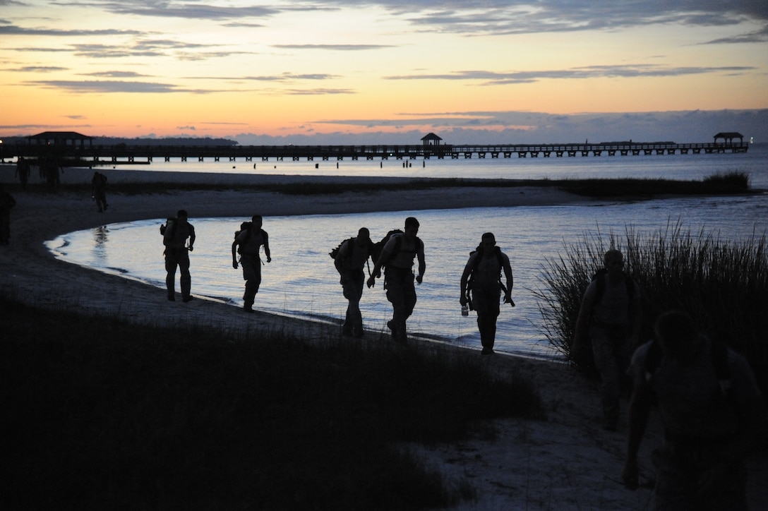 Members of the 334th Training Squadron combat controllers and the 335th Training Squadron special operations weather team participate in a memorial physical training session Sept. 26, 2014, Ocean Springs, Miss., with a ruck march along the Ocean Springs Beach and over the Biloxi/Ocean Springs Bridge. The PT event was in memory of combat controller Senior Airman Mark Forester who was killed in action on Sept. 29, 2010, and Senior Airman Daniel Sanchez who was killed in action Sept. 16, 2010.  (U.S. Air Force photo by Kemberly Groue)