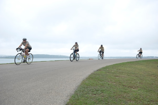 Four-member relay teams power through the 22-mile bike route Sept. 20, 2014 at the Rambler 120 Adventure Race at Joint Base San Antonio Recreation Park on Canyon Lake. Throughout the race, the first and last team member must stay within 50 yards of each other to avoid penalties. A six-mile run and two-mile raft race follow the 22-mile bike race. (U.S. Air Force photo by Airman Justine K. Rho/released)