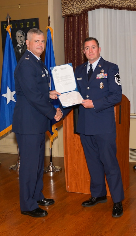 Col. Shawn Clouthier, 109th Airlift Wing commander, presents Master Sgt. Kyle DeFeo with the Certificate of Induction during a ceremony Sept. 25, 2014 at Schenectady County Community College, Schenectady, New York. The 109th AW Senior Noncommissioned Officer Induction Ceremony is an annual event held to recognize Airmen who were recently promoted to the rank of master sergeant. DeFeo is assigned to the 109th Security Forces Squadron at Stratton Air National Guard Base. (U.S. Air National Guard photo by Master Sgt. William Gizara/Released)