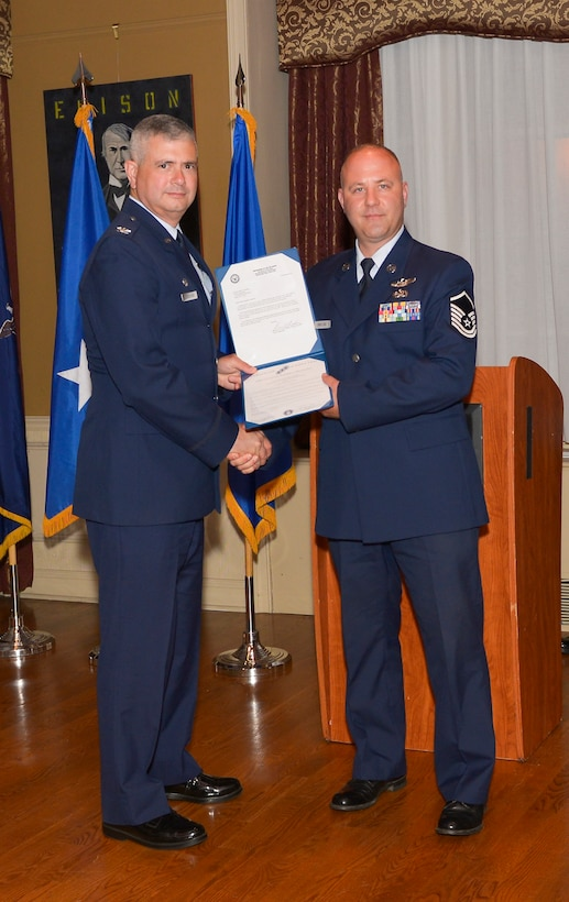 Col. Shawn Clouthier, 109th Airlift Wing commander, presents Master Sgt.Daniel Swatling with the Certificate of Induction during a ceremony Sept. 25, 2014 at Schenectady County Community College, Schenectady, New York. The 109th AW Senior Noncommissioned Officer Induction Ceremony is an annual event held to recognize Airmen who were recently promoted to the rank of master sergeant. Swatling is assigned to the 109th Operations Group at Stratton Air National Guard Base. (U.S. Air National Guard photo by Master Sgt. William Gizara/Released)