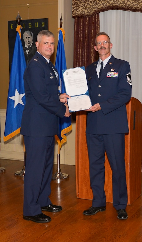 Col. Shawn Clouthier, 109th Airlift Wing commander, presents Master Sgt. Stephen Radz with the Certificate of Induction during a ceremony Sept. 25, 2014 at Schenectady County Community College, Schenectady, New York. The 109th AW Senior Noncommissioned Officer Induction Ceremony is an annual event held to recognize Airmen who were recently promoted to the rank of master sergeant. Radz is assigned to the 109th Maintenance Group at Stratton Air National Guard Base. (U.S. Air National Guard photo by Master Sgt. William Gizara/Released)