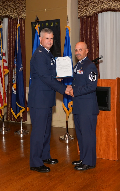 Col. Shawn Clouthier, 109th Airlift Wing commander, presents Master Sgt. Keith Eriole with the Certificate of Induction during a ceremony Sept. 25, 2014 at Schenectady County Community College, Schenectady, New York. The 109th AW Senior Noncommissioned Officer Induction Ceremony is an annual event held to recognize Airmen who were recently promoted to the rank of master sergeant. Eriole is assigned to the 109th Force Support Squadron at Stratton Air National Guard Base. (U.S. Air National Guard photo by Master Sgt. William Gizara/Released)