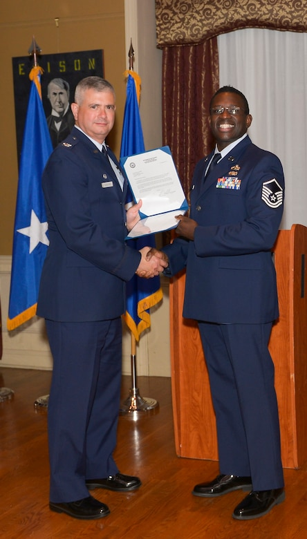 Col. Shawn Clouthier, 109th Airlift Wing commander, presents Master Sgt. David Ricks with the Certificate of Induction during a ceremony Sept. 25, 2014 at Schenectady County Community College, Schenectady, New York. The 109th AW Senior Noncommissioned Officer Induction Ceremony is an annual event held to recognize Airmen who were recently promoted to the rank of master sergeant. Ricks is assigned to the 109th Maintenance Group at Stratton Air National Guard Base. (U.S. Air National Guard photo by Master Sgt. William Gizara/Released)