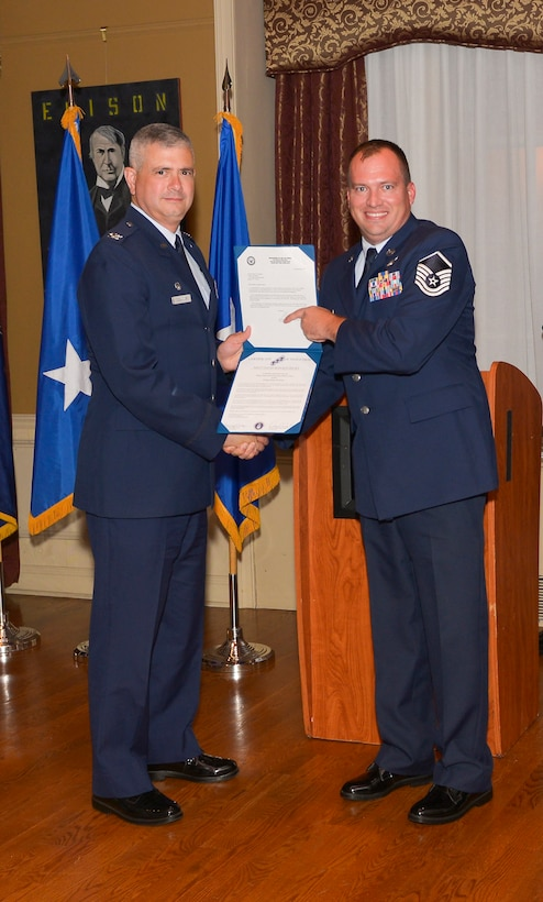 Col. Shawn Clouthier, 109th Airlift Wing commander, presents Master Sgt. Bret Backus with the Certificate of Induction during a ceremony Sept. 25, 2014 at Schenectady County Community College, Schenectady, New York. The 109th AW Senior Noncommissioned Officer Induction Ceremony is an annual event held to recognize Airmen who were recently promoted to the rank of master sergeant. Backus is assigned to the 109th Maintenance Group at Stratton Air National Guard Base. (U.S. Air National Guard photo by Master Sgt. William Gizara/Released)