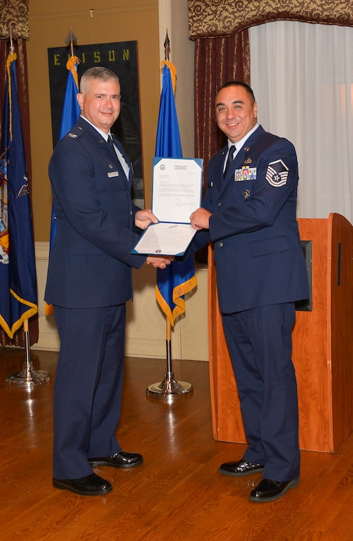 Col. Shawn Clouthier, 109th Airlift Wing commander, presents Master Sgt. Jim DuPuis with the Certificate of Induction during a ceremony Sept. 25, 2014 at Schenectady County Community College, Schenectady, New York. The 109th AW Senior Noncommissioned Officer Induction Ceremony is an annual event held to recognize Airmen who were recently promoted to the rank of master sergeant. DuPuis is assigned to the 109th Security Forces Squadron at Stratton Air National Guard Base. (U.S. Air National Guard photo by Master Sgt. William Gizara/Released)