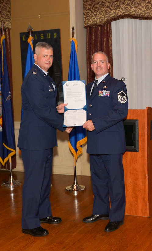 Col. Shawn Clouthier, 109th Airlift Wing commander, presents Master Sgt. Steven Chandler with the Certificate of Induction during a ceremony Sept. 25, 2014 at Schenectady County Community College, Schenectady, New York. The 109th AW Senior Noncommissioned Officer Induction Ceremony is an annual event held to recognize Airmen who were recently promoted to the rank of master sergeant. Chandler is assigned to the 109th Maintenance Group at Stratton Air National Guard Base. (U.S. Air National Guard photo by Master Sgt. William Gizara/Released)