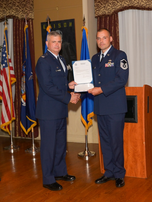 Col. Shawn Clouthier, 109th Airlift Wing commander, presents Master Sgt.Jeremy Muller with the Certificate of Induction during a ceremony Sept. 25, 2014 at Schenectady County Community College, Schenectady, New York. The 109th AW Senior Noncommissioned Officer Induction Ceremony is an annual event held to recognize Airmen who were recently promoted to the rank of master sergeant. Muller is assigned to the 109th Logistics Readiness Squadron at Stratton Air National Guard Base. (U.S. Air National Guard photo by Master Sgt. William Gizara/Released)
