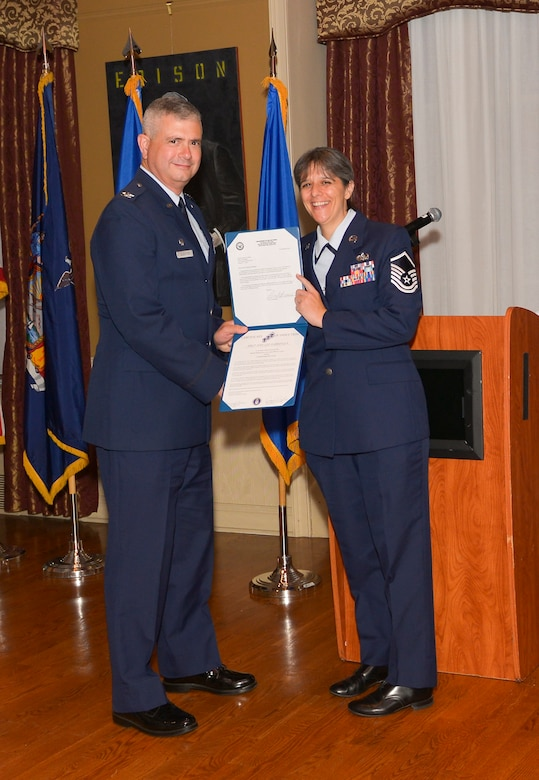 Col. Shawn Clouthier, 109th Airlift Wing commander, presents Master Sgt. Jodi Habbinger with the Certificate of Induction during a ceremony Sept. 25, 2014 at Schenectady County Community College, Schenectady, New York. The 109th AW Senior Noncommissioned Officer Induction Ceremony is an annual event held to recognize Airmen who were recently promoted to the rank of master sergeant. Habbinger is assigned to the 109th Communications Flight at Stratton Air National Guard Base. (U.S. Air National Guard photo by Master Sgt. William Gizara/Released)