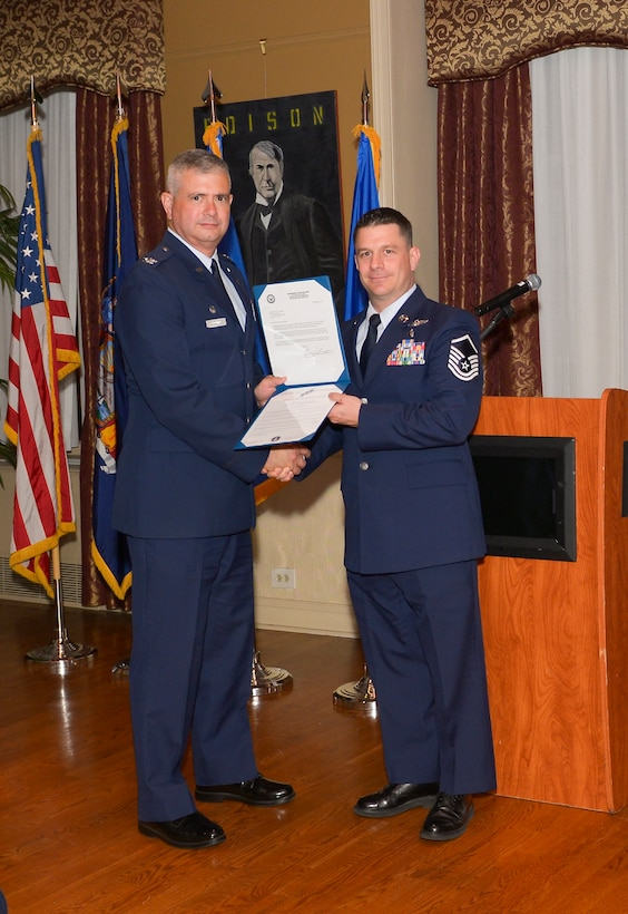 Col. Shawn Clouthier, 109th Airlift Wing commander, presents Master Sgt.Joseph Smith with the Certificate of Induction during a ceremony Sept. 25, 2014 at Schenectady County Community College, Schenectady, New York. The 109th AW Senior Noncommissioned Officer Induction Ceremony is an annual event held to recognize Airmen who were recently promoted to the rank of master sergeant. Smith is assigned to the 109th Operations Group at Stratton Air National Guard Base. (U.S. Air National Guard photo by Master Sgt. William Gizara/Released)