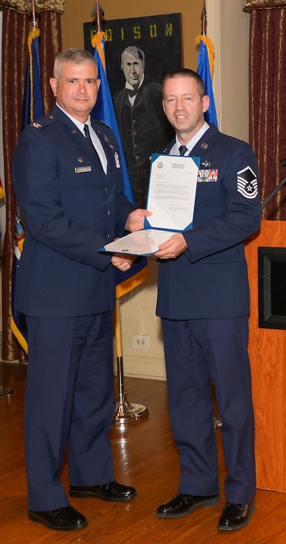 Col. Shawn Clouthier, 109th Airlift Wing commander, presents Master Sgt. Scott Molyneaux with the Certificate of Induction during a ceremony Sept. 25, 2014 at Schenectady County Community College, Schenectady, New York. The 109th AW Senior Noncommissioned Officer Induction Ceremony is an annual event held to recognize Airmen who were recently promoted to the rank of master sergeant. Molyneaux is assigned to the 109th Logistics Readiness Squadron at Stratton Air National Guard Base. (U.S. Air National Guard photo by Master Sgt. William Gizara/Released)