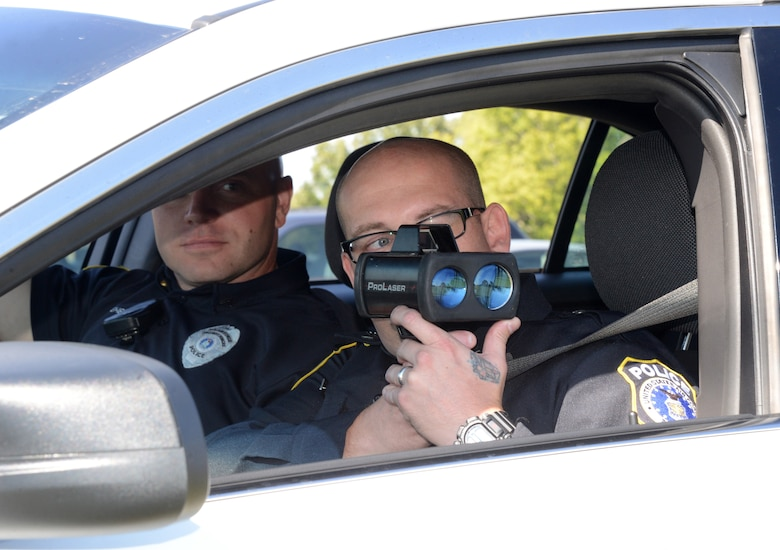 Sgt. Michael Biddy, front, and Corporal Aaron Whitehead use a radar gun to detect the speed limit of drivers on Tinker Air Force Base. The two DAF civilian police officers were both prior military before joining the civilian security forces here on base. Civilian officers are federally certified law enforcement officers and perform the same duties as the military security forces. (Air Force photo by Kelly White)