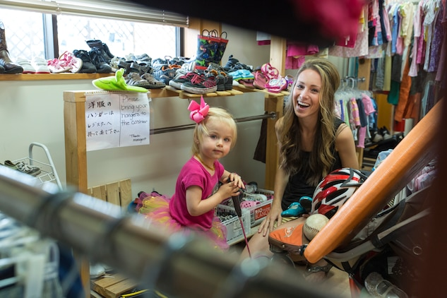 Kayla Porter and her daughter, Brielle, search for shoes at the Marine Thrift Store during Customer Appreciation Day, Sept. 27, 2014, aboard Marine Corps Air Station Iwakuni, Japan. Attractions included free food, raffle prizes, a live DJ, face painting, a bounce house and more as a way for the thrift store to thank the community.