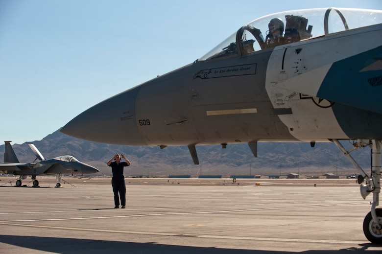 Staff Sgt. Justin White signals to Maj. Sam Joplin to begin taxiing a 65th Aggressor Squadron F-15 Eagle to the runway Sept. 18, 2014, at Nellis Air Force Base Nev. The roles and responsibilities of the 65th AGRS, deactivated Sept. 26, 2014, will be filled by the 64th AGRS. White is a crew chief with the 757th Aircraft Maintenance Squadron's Flanker Aircraft Maintenance Unit and Joplin is an F-15 pilot with the 122nd Fighter Squadron at Naval Air Station Joint Reserve Base New Orleans. (U.S. Air Force photo/Airman 1st Class Thomas Spangler)