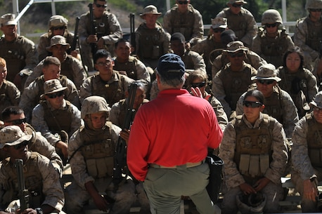 Craig Fairbanks, the leader instructor for the Shotgun Qualification Course explains the course to the Marines of Ammo Company, 1st Supply Battalion aboard Marine Corps Base Camp Pendleton, Calif., Sept. 15, 2014. The range required the Marines to demonstrate proficiency with the M1014 shotgun. The live-fire ranges were part of an annual training package to keep the Marines confident and proficient with each weapon system.