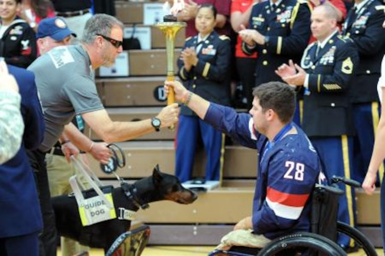 Army Sgt. First Class Doug Franklin of the Army Special Operations Command team passes the Olympic torch to retired Marine Cpl. Paul Schaus, who is a gold medal Paralympian, during the opening ceremony for the 2014 Warrior Games at the Olympic Training Center in Colorado Springs, Colo., Sept. 28, 2014. (DoD News photo by EJ Hersom)