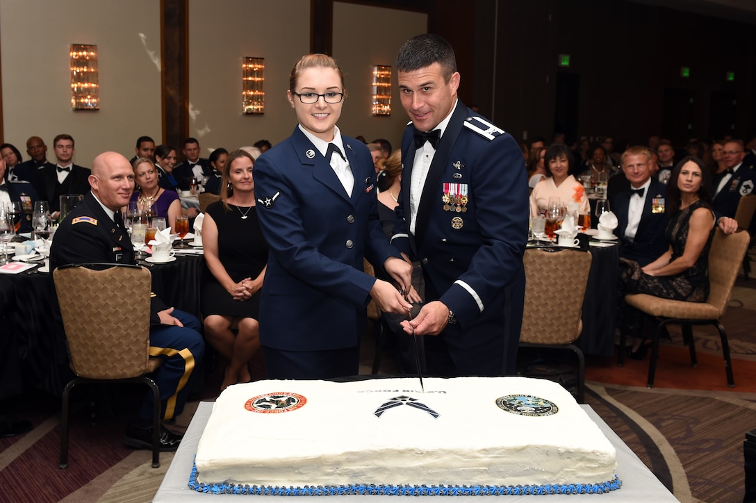 Airman Emily E. Amyotte, 460th Space Wing Public Affairs photojournalist, left, and Col. John Wagner, 460th Space Wing commander, cut the cake during the Air Force Ball and 460th Space Wing 10th anniversary celebration Sept. 27, 2014, at the Grand Hyatt Hotel in Denver. Every year, the Air Force celebrates its birthday with a formal military ball and festivities many people remember for a lifetime. Buckley Air Force Base did their part to wish the Air Force and the 460th SW a happy birthday with dinner, a guest speaker and a nighttime celebration. (U.S. Air Force photo by Airman Emily E. Amyotte/Released)
